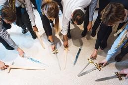 Workshop-Teilnehmer legen Schwerter vor sich auf den Boden.